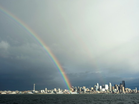 Aaron  McCoy-a-rainbow-lands-on-a-washington-state-ferry-in-the-puget-sound-with-the-seattle-skyline-in-the-back