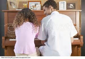 Father and daughter playing the piano. Courtesy of visualphotos[dot]com